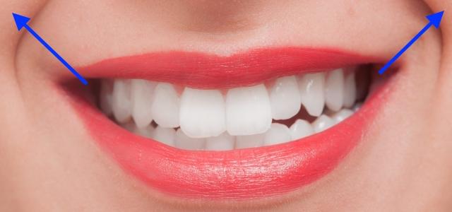 上の歯を見せるように歌う